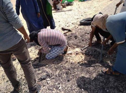Des manifestants du Polisario arrachant des morceaux du bitume de la route à El Guerguerate. / DR