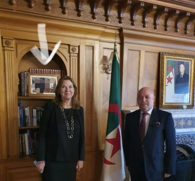 The Algerian and Swedish ambassadors standing before a blurred photo that shows King Mohammed VI and the Algerian diplomat. / DR