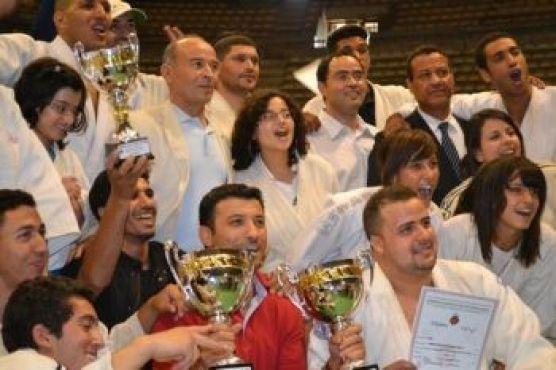 et se joint à l'équipe entière, qui célèbre cette double victoire autour d'Adil Belgaid (en rouge), fondateur du club.