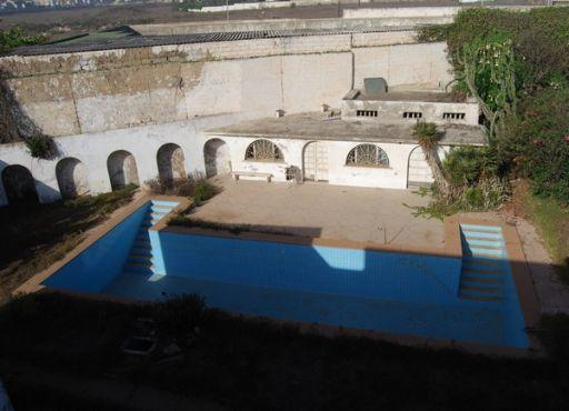 Dans le jardin, laissé à l'abandon, a été creusée une grande piscine.