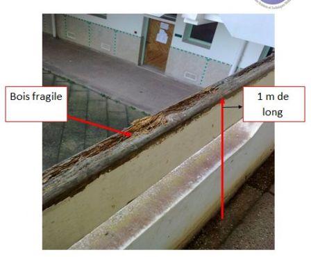 Photo montrant en détail la balustrade en bois qui a cédé après que trois étudiants se soient adossés dessus.