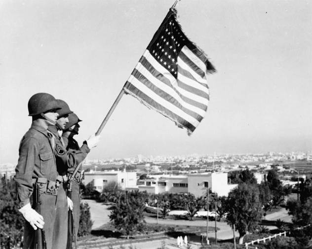 Des soldats américains brandissant le drapeau des Etats-Unis à Casablanca le 11 novembre 1942 lors de la Deuxième Guerre mondiale. / DR